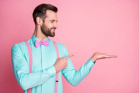 Photo of handsome macho guy trend clothes beaming smile hold open arm direct finger showing novelty product wear teal shirt suspenders bow tie isolated pastel pink color background