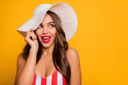 Closeup photo of charming lady long hairdo bronze body skin sensual plump lips look flirty empty space wear sun headwear white red striped bodysuit isolated bright yellow color background