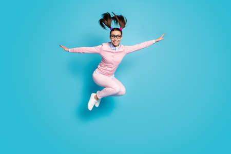 Full size photo of cheerful high school student girl jump hold hand imagine she fly plane academic lesson wear pink clothes sneakers isolated over blue color background