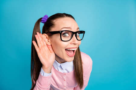 Close up photo of astonished funny funky teen college student girl hold hand ear listen incredible rumors wear pink shirt jumper isolated over blue color background