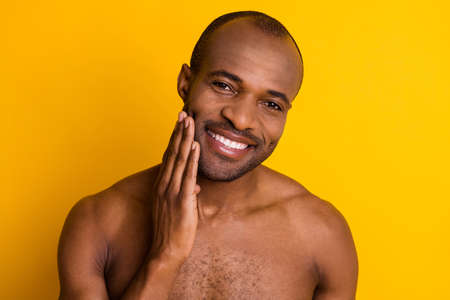 Closeup photo of cheerful dark skin guy good mood hold arm on cheek look mirror amazing after shaving lotion result naked muscle body isolated bright yellow color background