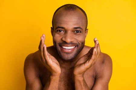 Close up photo of positive afro american guy wash water his face after shaving procedure enjoy hygiene isolated over bright color background 写真素材