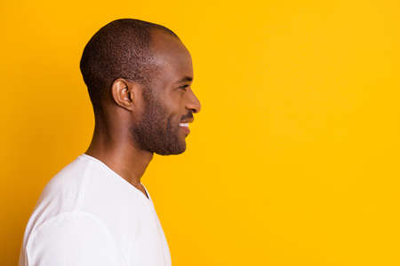 Closeup profile photo of attractive cheerful dark skin guy good mood beaming smile look empty space wear casual white t-shirt isolated bright vivid yellow color background