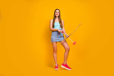 Full length body size view of nice attractive lovely cheerful straight-haired girl holding in hands festive love arrows isolated on bright vivid shine vibrant yellow color background