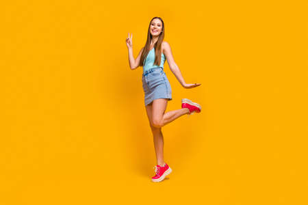Full length body size view of nice attractive lovely pretty cheerful cheery straight-haired girl having fun showing v-sign isolated over bright vivid shine vibrant yellow color background