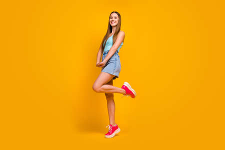 Full length body size view of nice attractive lovely winsome lovable cheerful cheery straight-haired girl posing having fun isolated over bright vivid shine vibrant yellow color background