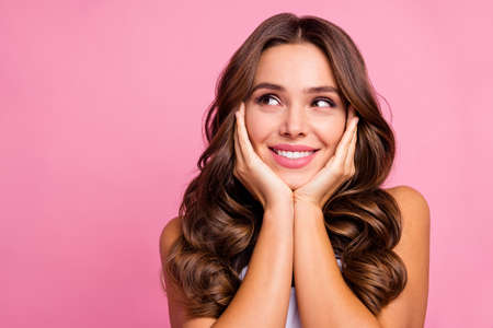 Closeup photo of pretty funny wavy lady overjoyed facial expression arms on cheeks look empty space dreamer wear white casual singlet isolated bright pink color background