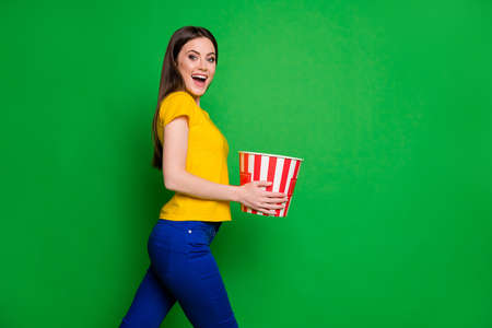 Profile side photo of positive cheerful girl hear her favorite series start hold big pop corn box go walk watch living room wear stylish trousers isolated over bright color background Banco de Imagens