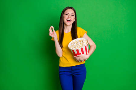 Portrait of positive cheerful girl hold big popcorn box watch funny series laugh wear yellow pants isolated over shine color background