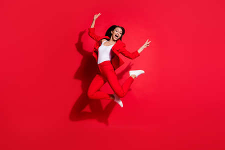Full length photo of attractive lady having fun jumping high up good mood showing v-sign symbols hands wear blazer suit pants footwear isolated bright red color background