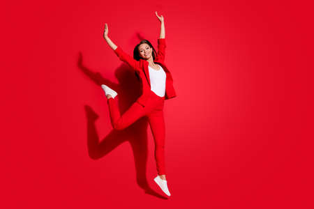 Full size photo of attractive funny lady successful worker having fun jumping high up good mood rejoicing wear blazer suit pants footwear isolated vibrant red color background