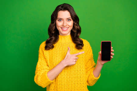 Photo of attractive lady holding telephone directing finger device advertising new smart phone model demonstrate interface wear yellow knitted jumper isolated green color background