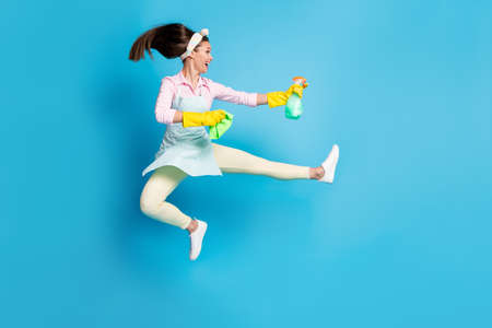 Full length body size view of her she nice attractive pretty funky funny comic childish cheerful maid jumping fighting infection dust isolated on bright vivid shine vibrant blue color background