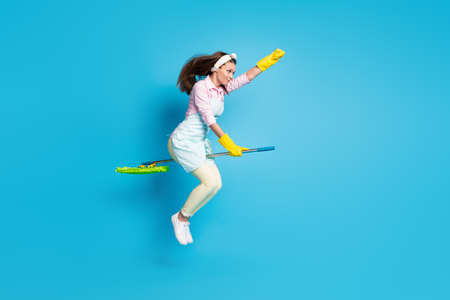 Full length body size view of her she nice attractive strong focused girl maid striving jumping riding broom motivation energy isolated on bright vivid shine vibrant blue color background Stock Photo