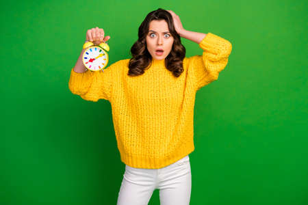 Oh no. Photo of crazy troubled lady hold colorful alarm clock check time late work hand on head wear knitted yellow pullover white pants isolated bright green color background