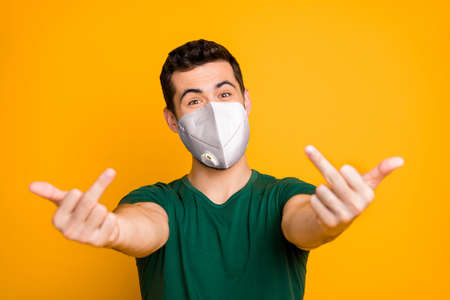 Close-up portrait of his he naughty healthy guy showing offensive sign middle finger wearing safety n95 mask stop viral disease mers cov pandemia health care isolated vibrant yellow color background