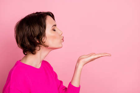 Closeup profile photo of pretty charming lady hold palm arm hand sending air kiss empty space eyes closed sincere feelings wear casual sweater pullover isolated pink pastel color background