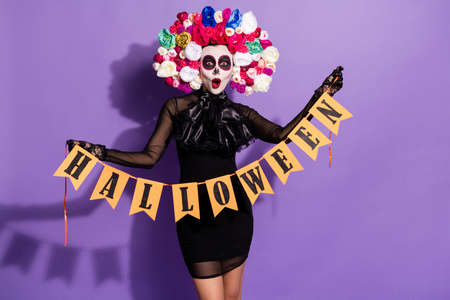 Photo of funny dead katrina bride lady face print traditional holiday hold halloween flags hang wall garland decor floral rose headband wear black costume isolated purple color background Stock Photo