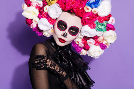 Closeup photo of hot sly dark dead beauty katrina calaverita facial print folklore creature saints honor mexican death day floral headwear traditional costume isolated purple color background Stock Photo