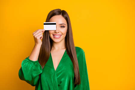 Close-up portrait of her she nice attractive pretty cute cheerful feminine straight-haired girl holding in hand plastic card closing eye isolated on bright vivid shine vibrant yellow color background 스톡 콘텐츠