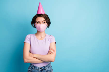 Photo of excited hipster girl in medical mask look copyspace covid news cross hands wear violet lilac t-shirt denim jeans isolated over blue color background