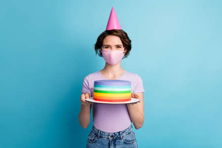 Portrait of positive cheerful girl in medical mask celebrate covid quarantine birthday hold cake wear cone lilac violet denim jeans isolated over blue color background