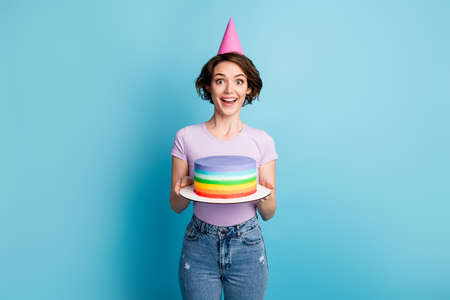 Portrait of astonished positive cheerful girl impressed friend party birthday preparation hold cake wear cone violet lilac clothes isolated over blue color background