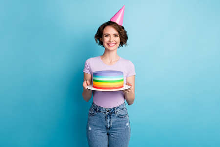 Portrait of positive cheerful girl hold bright cake celebrate birthday anniversary wear cone good look clothes isolated over blue color background