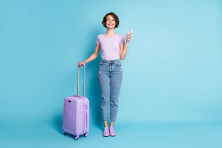 Full size photo of positive cheerful girl tourist hold baggage use smartphone booking taxi hotel wear lilac violet t-shirt denim jeans isolated blue color background