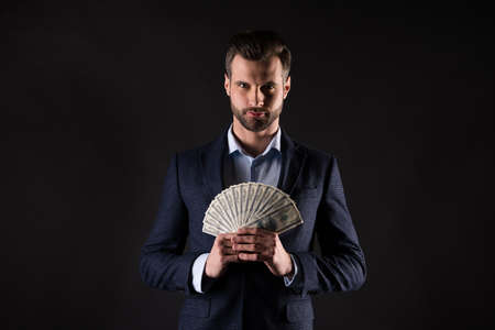 Photo of attractive handsome business guy hold hands fan of usa bucks rich person successful millionaire wear blue costume blazer shirt isolated black color background