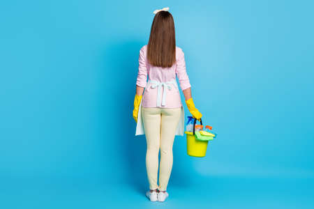 Full length rear behind photo of pretty lady house wife hold equipment disinfection bucket clean apartment wear headband latex gloves apron shirt pants shoes isolated blue color background