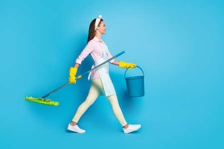 Full size profile side photo of positive professional cleaner worker girl hold mop bucket ready disinfect house covid infection wear pink shirt pants trousers isolated blue color background