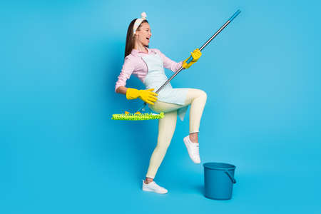 Full length photo of crazy funky hipster girl wash floor play mop guitar imagine she rock star wear pink shirt pants trousers yellow gloves isolated over blue color background
