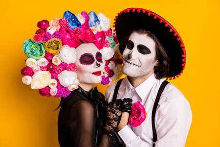 Everlasting love. Closeup photo of cute lovely dead couple man lady hold hands wear black lace dress gloves death costume roses headband suspenders sombrero isolated yellow color background