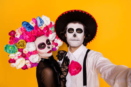 Closeup portrait photo of pretty undead creature couple man lady take selfie wear black lace dress gloves death costume roses headband suspenders sombrero isolated yellow color background Stock Photo
