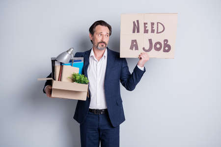 Looking for a job. Photo of unhappy worker mature guy financial crisis lost work hold carton box belongings quit hold placard banner search work place wear suit isolated grey background