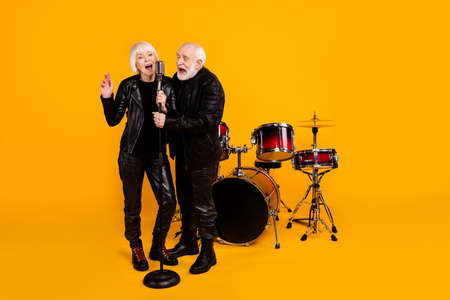 Portrait of his he her she nice attractive cheerful cheery grey-haired couple friends singing hit romantic single restaurant isolated over bright vivid shine vibrant yellow color background