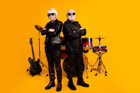 Portrait of his he her she nice attractive content serious grey-haired couple professional artist folded arms garage group isolated over bright vivid shine vibrant yellow color background