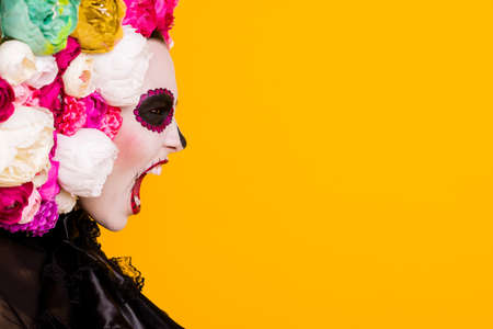 Profile headshot photo of calavera katrina goddess disappointed human sacrifices yell open mouth wear black dress death carnival costume roses headband isolated yellow color background Stock Photo