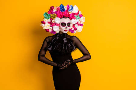 Dia de muertos. Photo of cute pretty young lady frightening look hold hands festival preparation wear black dress death carnival costume roses headband isolated yellow color background