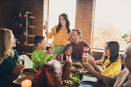 Photo of full family meeting sit served dinner served table hold wineglasses prepare drink make toast wish meet soon golden wine stewed fruits multi-generation in evening living room indoors