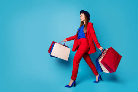 Full body profile photo of self-confident business lady boss walking shopping center holding many packs wear retro cap red suit shirt blazer pants high-heels isolated blue color background