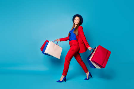 Full body profile photo of confident lady boss walk shopping center hold many packs wear retro cap red suit shirt blazer pants high-heels isolated blue color background Stock fotó
