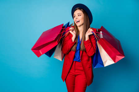 Photo of confident pretty business lady boss visiting shopping center holding many packs laughing out loud wear retro cap red suit blouse shirt blazer pants isolated blue color background
