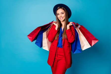 Photo of self-confident pretty business lady boss visiting shopping center holding many packs wear retro cap red suit blouse shirt blazer pants isolated blue color background