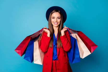 Photo of self-confident business lady boss visiting shopping center holding many packs wear retro cap red suit blouse shirt blazer pants high-heels isolated blue color background Stock fotó