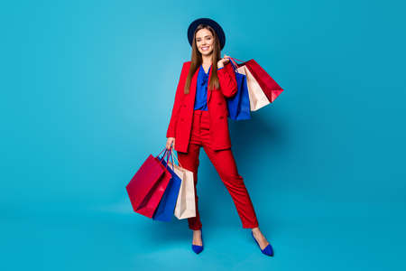 Full body photo of self-confident business lady boss visiting shopping center holding many packs wear retro cap red suit blouse shirt blazer pants high-heels isolated blue color background