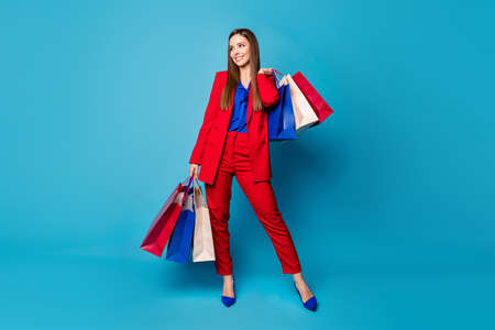 Full body photo of self-confident business lady boss visiting shopping center holding many packs wear red suit blouse shirt blazer pants high-heels isolated blue color background