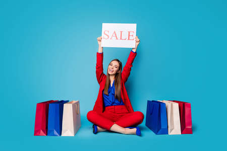 Full body photo of self-confident lady boss sitting floor shoes shopping bags raise sale placard wear red suit blouse shirt blazer trousers high-heels isolated blue color background