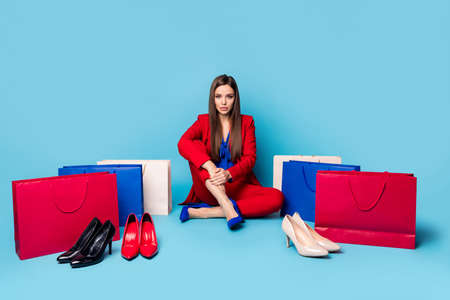 Full length photo of self-confident lady successful worker sitting near shoes shopping bags wear red suit blouse shirt blazer trousers high-heels isolated blue color background